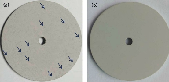 FIGURE 4 The appearance of MAO coatings formed in (a) additive-free and (b) 7 g/L additive-containing electrolyte after a salt solution immersion test in 5 wt% NaCl solution for 96 h. The coating formed in the additive-free electrolyte showed some scattered black areas (marked by the blue arrows).
