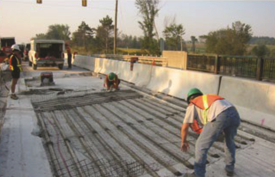 FIGURE 3 Installing distributed galvanic anodes and carbon fiber grid prior to installing concrete overlay.