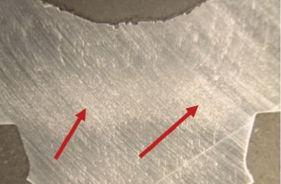 FIGURE 5 Longitudinal section of screw ground polished and etched revealed grain flow (red arrows).