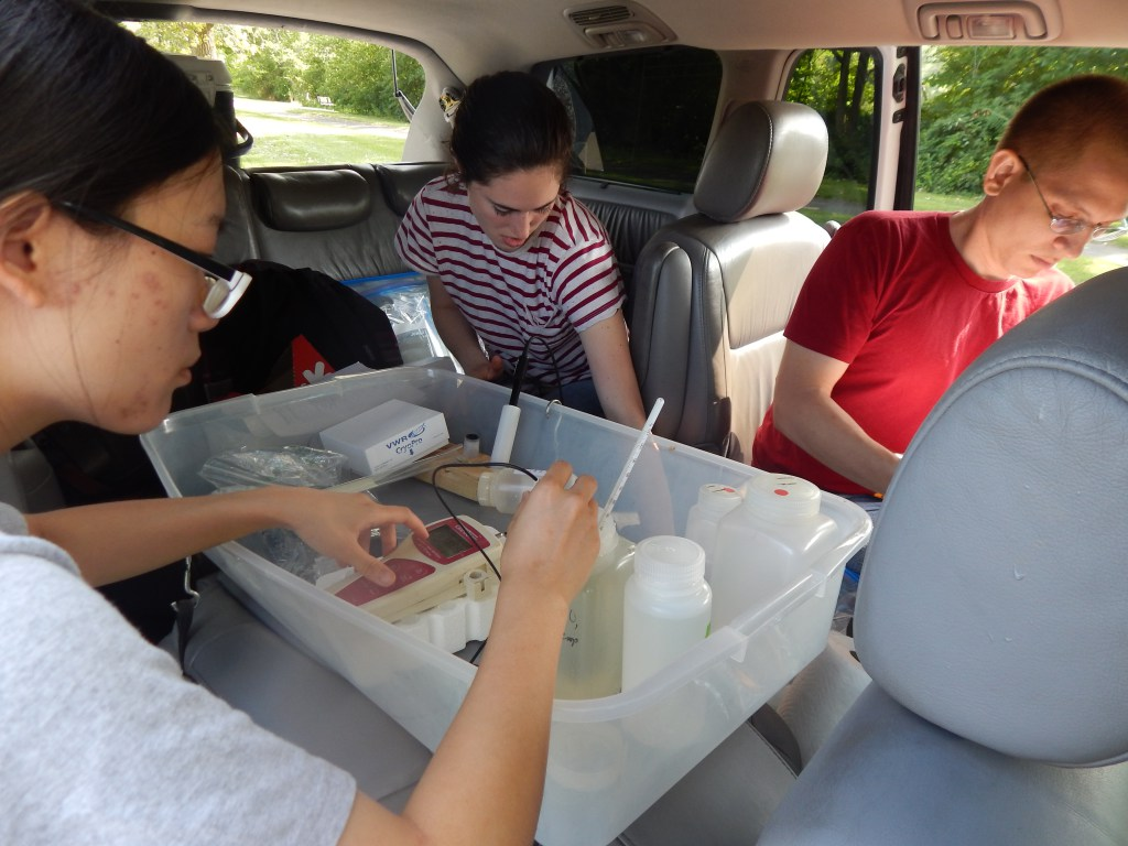 Min Tang, Bekah Martin, and Otto Schwake process chemical samples and take measurements in their mobile lab in Flint, Michigan. Photo credit: Flintwaterstudy.org.