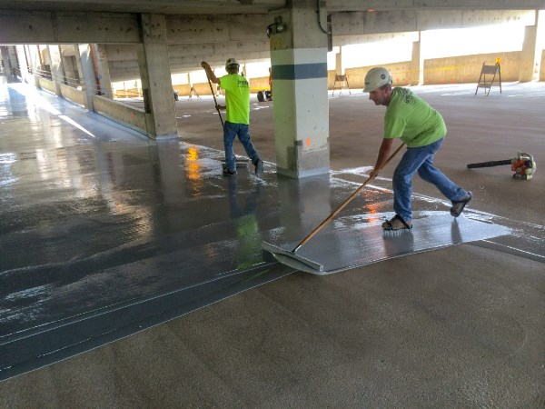 The installation of a protective waterproof membrane, as shown here, can prevent many future problems in concrete parking structures. Photo courtesy of Western Specialty Contractors.